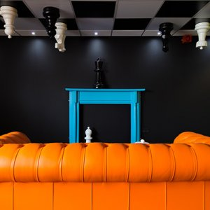 Being creative with chess board on the ceiling and bright orange sofa