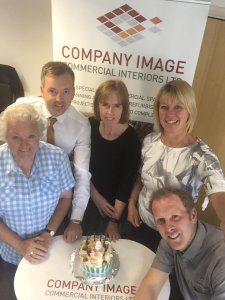 The Company Image team in the office celebrate with cake for our 8th birthday